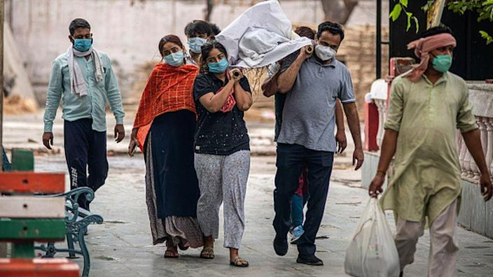 Relatives carry the body of a covid 19 victim at Ghazipur cremation ground on 18 May 2021