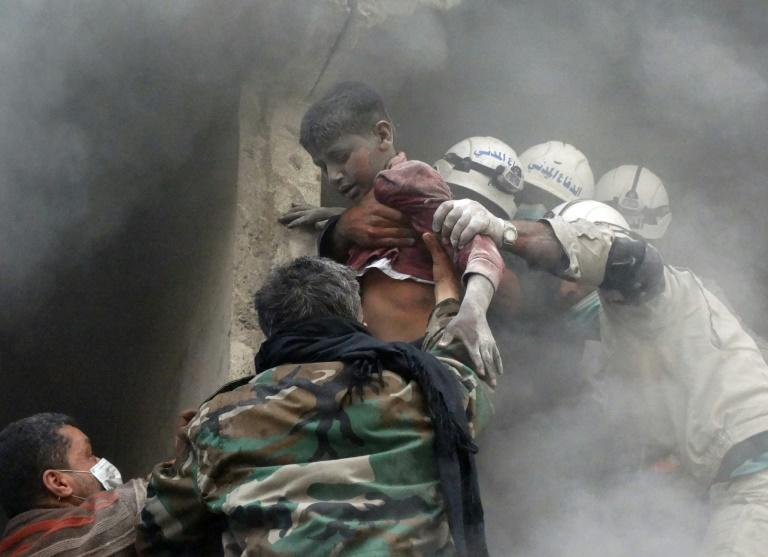 Emergency responders evacuate a Syrian boy from a residential building reportedly hit by a barrel bomb dropped by government forces in Aleppo's Shaar neighbourhood on April 6, 2014 (AFP Photo/KHALED KHATIB)