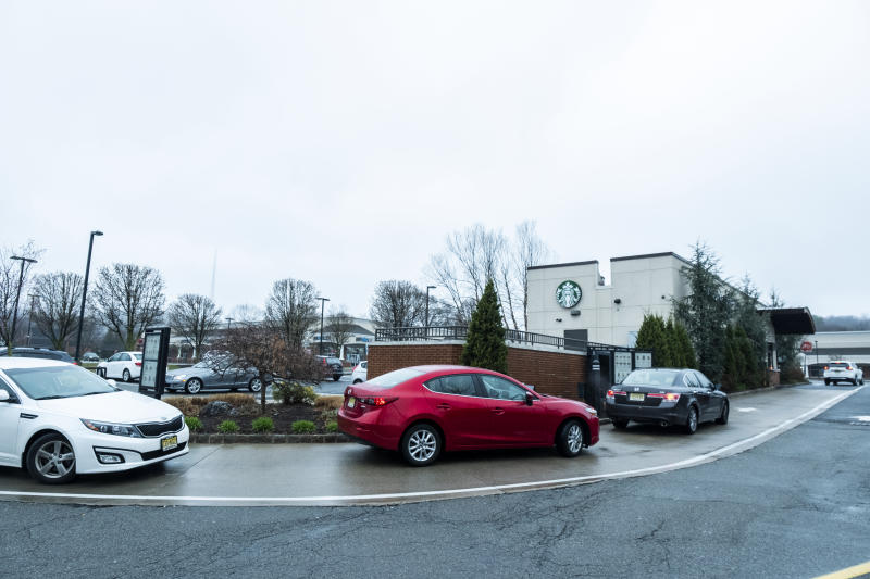 POMPTON LAKES, NJ - MARCH 29: A line of cars waits at Starbucks Drive Thru which his closed its cafe and is only operating their drive-thru from 6 AM to 2 PM on a Sunday afternoon. Earlier in the week Governor Phil Murphy announced a total 24-hour lockdown of the New Jersey residents after they did not take his stay-at-home orders seriously regarding the Coronavirus pandemic. The Governor also issued a statement saying that those that did not heed this would be prosecuted. Photographed in Pompton Lakes, NJ on March 29, 2020, USA. (Photo by Ira L. Black/Corbis via Getty Images)