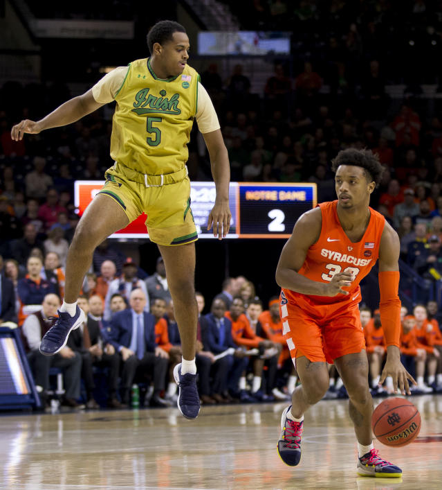 Syracuse's Elijah Hughes (33) moves by Notre Dame's D.J. Harvey (5) during the first half of an NCAA college basketball game Saturday, Jan. 5, 2019, in South Bend, Ind. Syracuse won 72-62. (AP Photo/Robert Franklin)