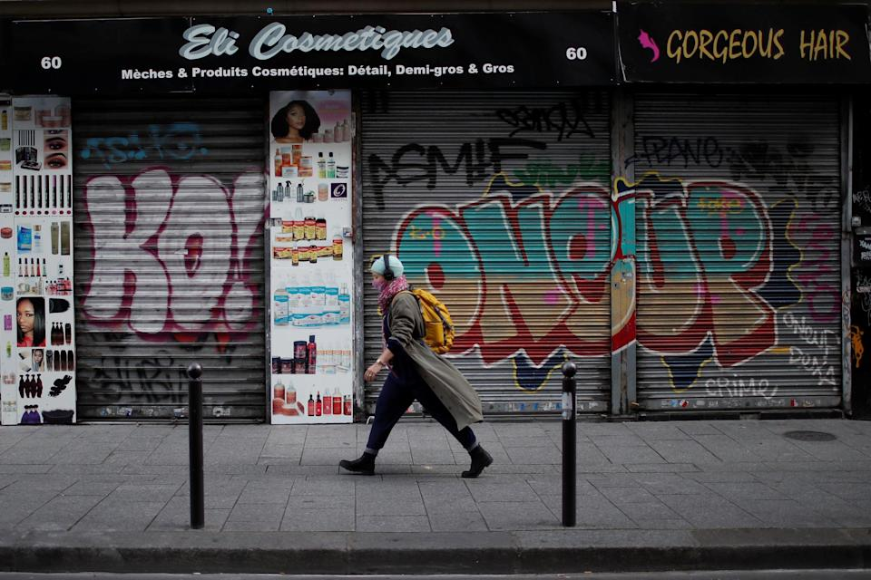 A woman walks past a closed hair and cosmetic shop in Paris during France's second national lockdown (REUTERS)