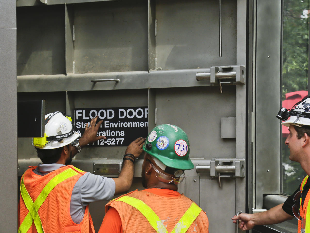"MTA workers place a ""flood door"" decal onto steel doors leading to the No. 1 train South Ferry subway station, Tuesday June 27, 2017, in New York. The station reopened Tuesday, nearly five years after it was flooded by Superstorm Sandy in October 2012. (AP Photo/Bebeto Matthews)"
