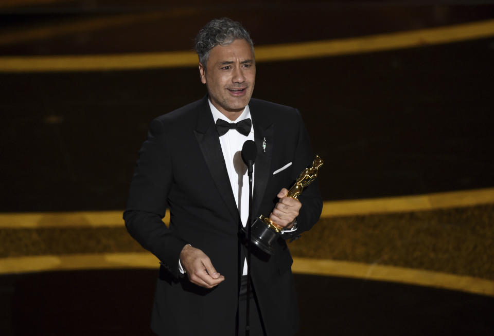"""Taika Waititi accepts the award for best adapted screenplay for """"Jojo Rabbit"""" at the Oscars on Sunday, Feb. 9, 2020, at the Dolby Theatre in Los Angeles. (AP Photo/Chris Pizzello)"""