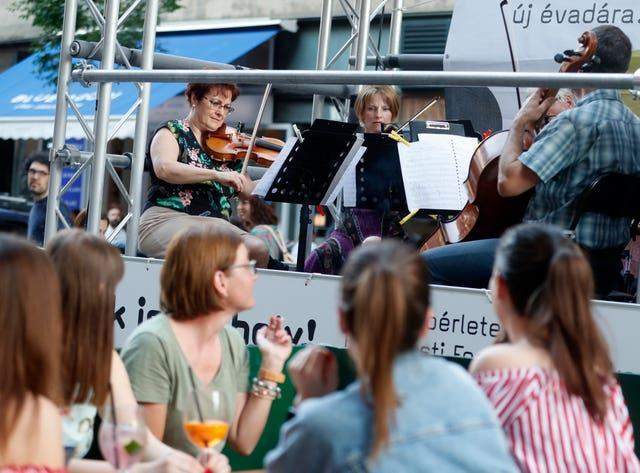 Members of the Budapest Festival Orchestra play music on the back of a truck while driving through the city