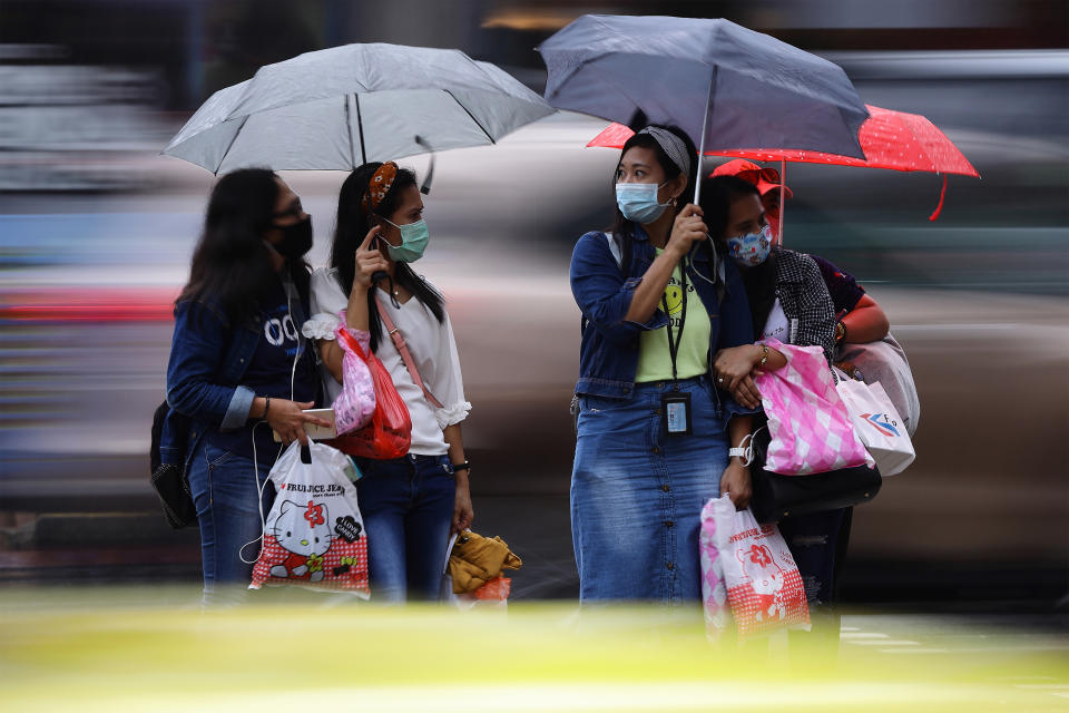 People seen waiting in the rain to cross a street in Singapore on 10 January. (PHOTO: Getty Images)