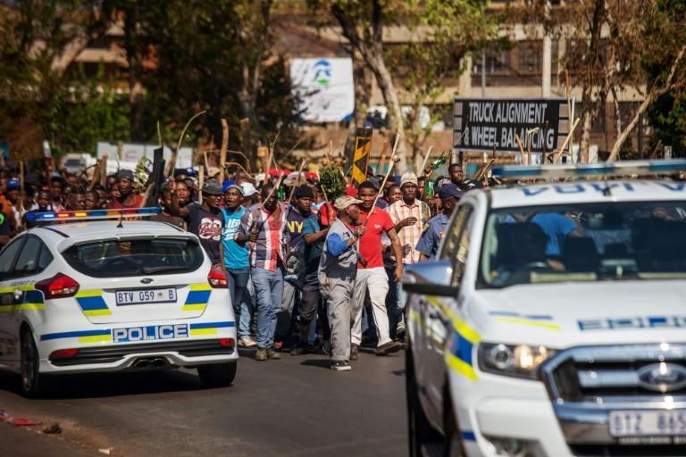 Hordes of people -- some armed with axes and machetes -- gathered in Johannesburg's central business district for a third day of unrest directed against foreigners