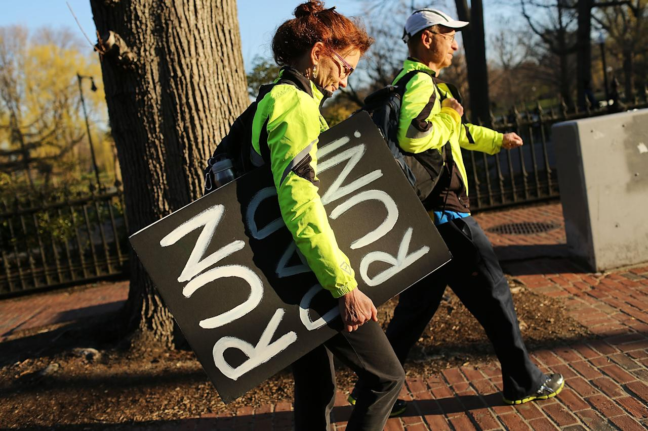 BOSTON, MA - APRIL 16: Claire Schaeffer Dufy walks with a sign she made to support her runner husband, Scott, near the scene of a twin bombing at the Boston Marathon on April 16, 2013 in Boston, Massachusetts. The twin bombings, which occurred near the marathon finish line, resulted in the deaths of three people while hospitalizing at least 128. The bombings at the 116-year-old Boston race, resulted in heightened security across the nation with cancellations of many professional sporting events as authorities search for a motive to the violence.  (Photo by Spencer Platt/Getty Images)
