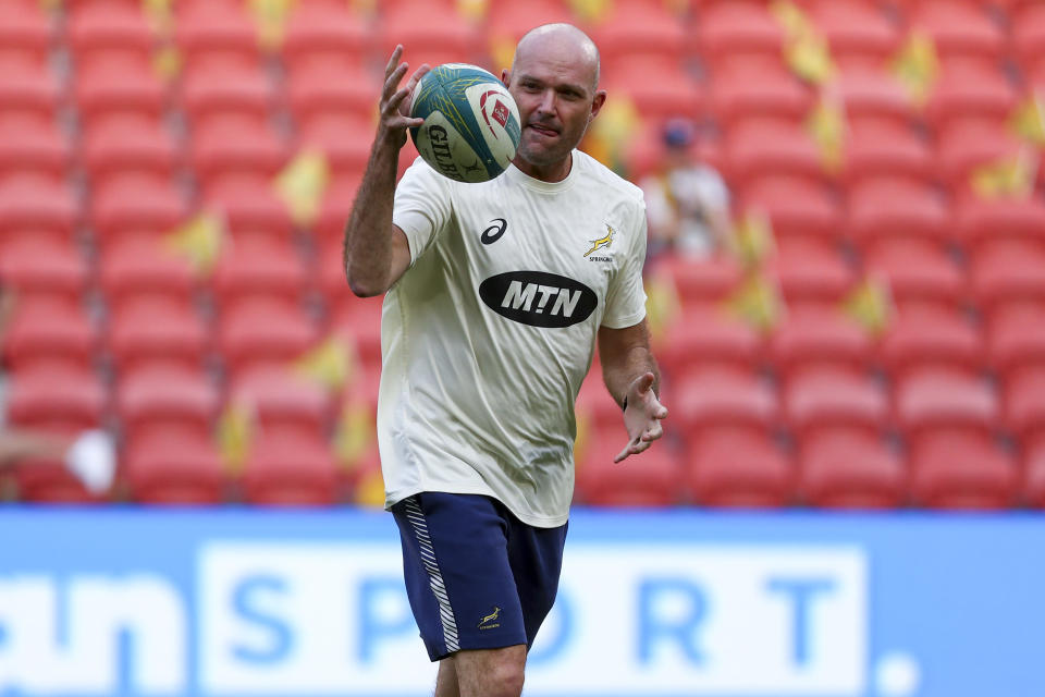 South Africa's coach Jacques Nienaber catches the ball as he watches his players warm up ahead of the Rugby Championship test match between the Springboks and the Wallabies in Brisbane, Australia, Saturday, Sept. 18, 2021. (AP Photo/Tertius Pickard)