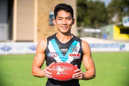 Port Adelaide Australian Rules football club's international academy recruit Chen Shaoliang from China poses with an AFL ball in Adelaide, Australia, March 21, 2017. Port Adelaide Football Club/Handout via REUTERS.