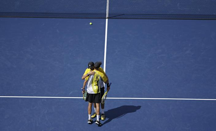 Bob and Mike Bryan, foreground, hug after losing to Radek Stepanek, of Czech Republic, and Leander Paes, of India, during the men's doubles semifinals of the 2013 U.S. Open tennis tournament, Thursday, Sept. 5, 2013, in New York. (AP Photo/David Goldman)