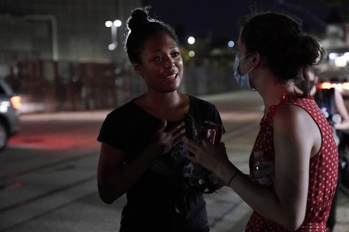 Adelana Akindes, left, reacts after being released from a day in police custody Thursday, Aug. 27, 2021, in Kenosha, Wis. Protesters gathered for a fifth night in reaction to the police shooting of Jacob Blake. (AP Photo/Morry Gash)