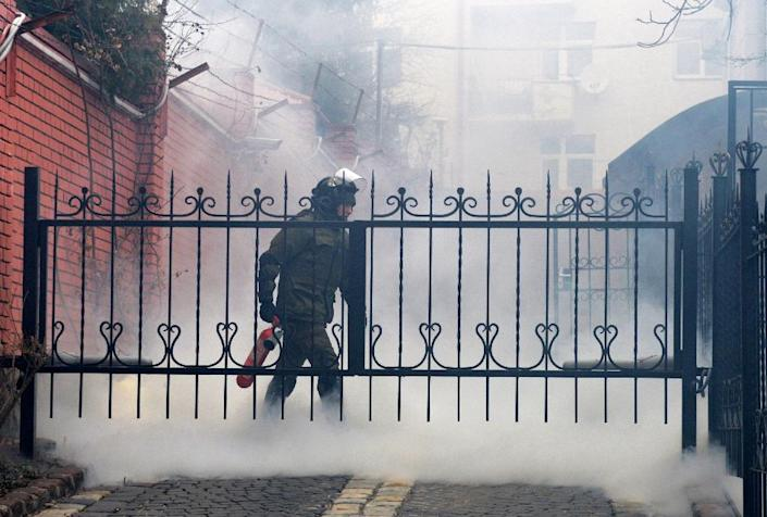 A member of security forces extinguishes a smoke bomb at the Russian consulate in Lviv, western Ukraine, during a rally in support of jailed Ukrainian military pilot Nadiya Savchenko on March 9, 2016 (AFP Photo/Yuriy Dyachyshyn)