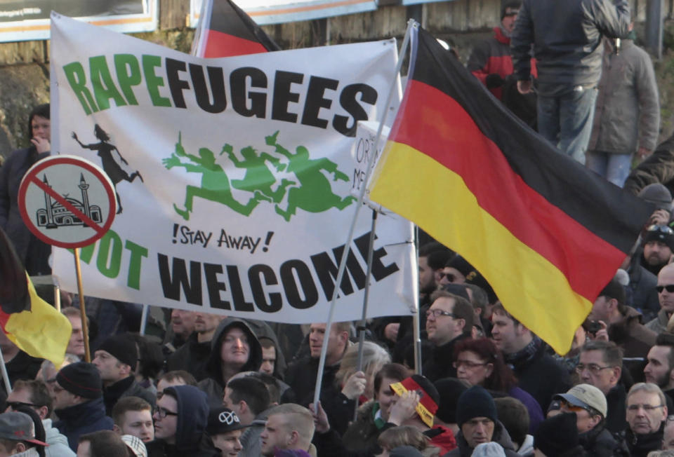 """FILE - In this Saturday Jan. 9, 2016 file photo, right-wing demonstrators hold a sign which reads, """"Rapefugees not welcome - !Stay away!"""" and a sign with a crossed out mosque as they march in Cologne, Germany. Women's rights activists, far-right demonstrators and left-wing counter-protesters all took to the streets of Cologne on Saturday in the aftermath of a string of New Year's Eve sexual assaults and robberies in Cologne blamed largely on foreigners. (AP Photo/Juergen Schwarz, File)"""