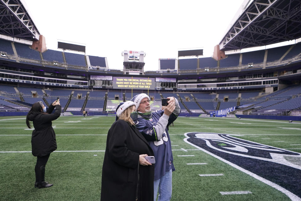 """Tom Gallagher, right, wears a Seattle Seahawks jersey and holiday hat as he takes a photo with his wife Debbie on the turf at Lumen Field, Thursday, Feb. 18, 2021, in Seattle. The couple, who are Seattle Seahawks season ticket holders, were celebrating their 45th anniversary by taking part in the """"Field To Table"""" event at the Seahawks' home stadium on the first night of several weeks of dates that offer four-course meals cooked by local chefs and served at socially distanced tables in an open-sided tent on the field as a precaution against the COVID-19 pandemic. (AP Photo/Ted S. Warren)"""