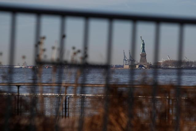The Statue of Liberty is seen through fencing from its ferry dock following a U.S. government shutdown in Manhattan, New York, U.S., January 20, 2018. REUTERS/Andrew Kelly