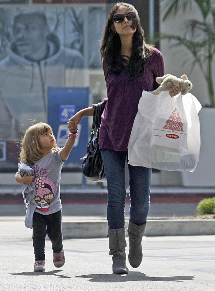 FILE - In this Sept. 29, 2011 file photo, a woman and child leave a mall with purchases in Culver City, Calif. The U.S. economy grew more slowly in the summer than previously thought because consumers spent less than the government had first estimated. But economists expect growth in the current October-December quarter to be stronger. (AP Photo/Reed Saxon)