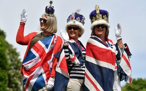 Royal fans bedecked with Union flags and crowns pose for a photograph on the Long Walk in Windsor - Credit: BEN STANSALL /AFP
