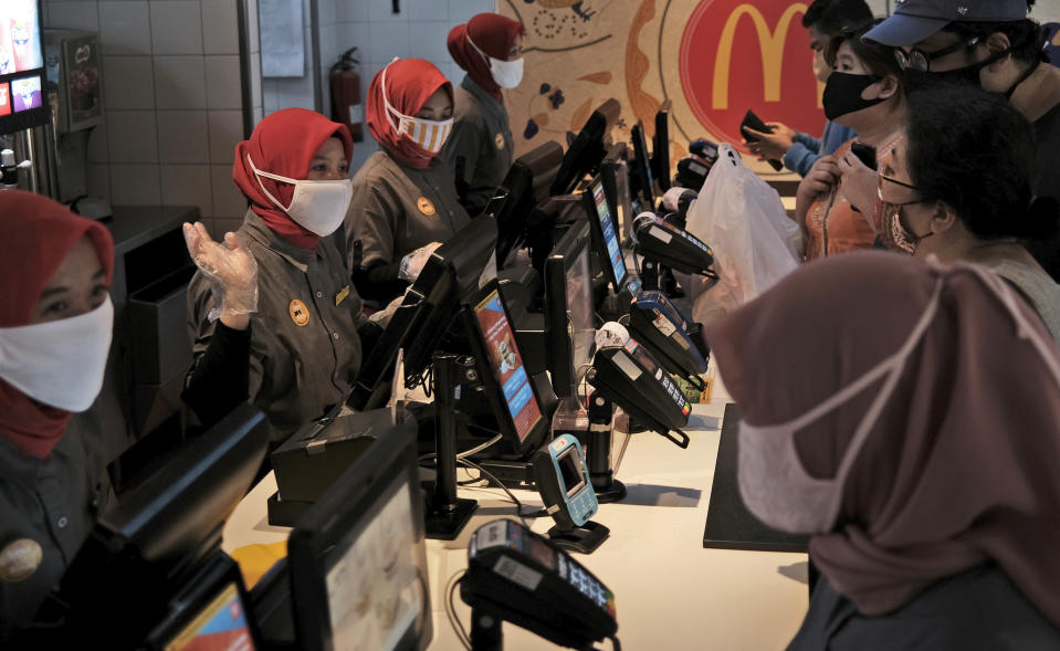 Employees wearing face masks as a precaution against the new coronavirus outbreak serve customers at a McDonald's restaurant in Jakarta, Indonesia, Sunday, May 10, 2020. (AP Photo/Dita Alangkara)