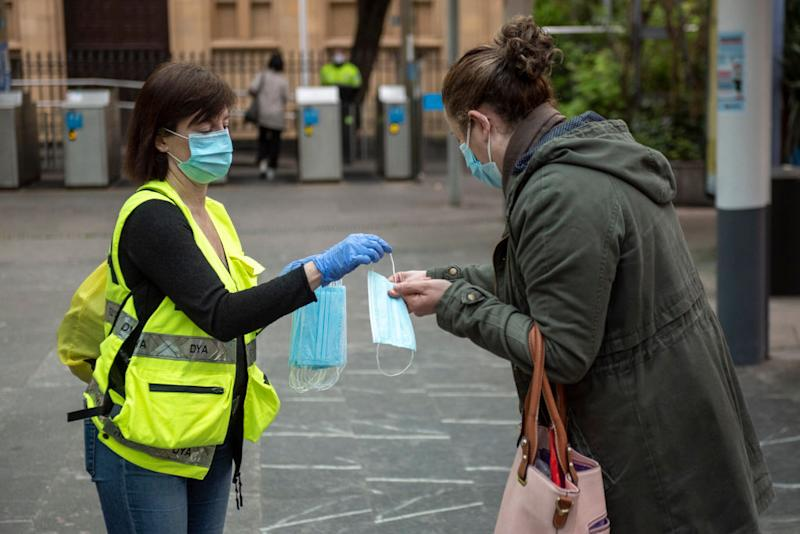 A woman in Spain's San Sebastian hands out masks to the public as lockdown measures are eased. Source: Getty