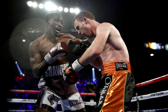 Terence Crawford, left, lands a punch on Jeff Horn, of Australia, in a welterweight title boxing match, Saturday, June 9, 2018, in Las Vegas. (AP Photo/John Locher)