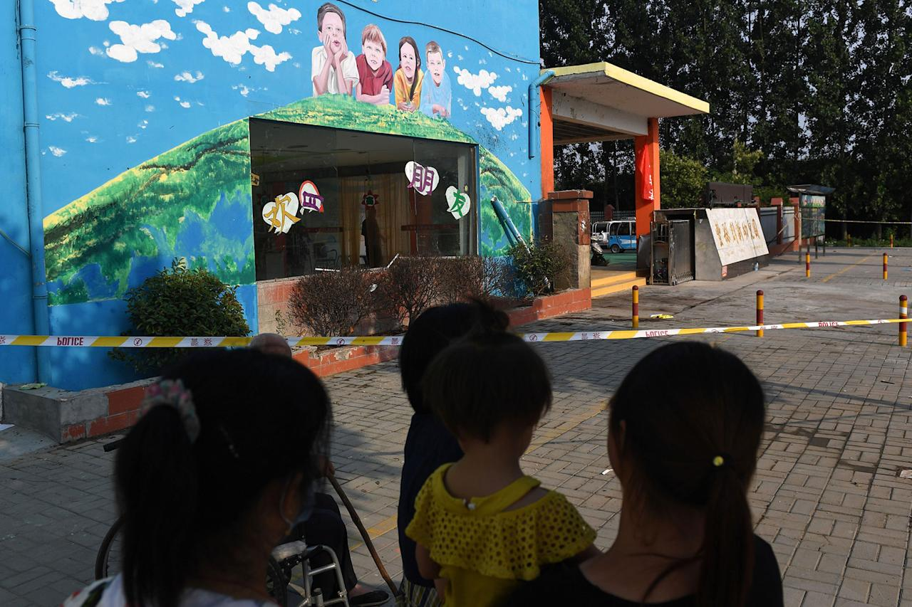 <p>Residents stand outside the gate of a kindergarten, where an explosion occurred a day earlier, in Fengxian in China's eastern Jiangsu province on June 16, 2017. (Photo: Greg Baker/AFP/Getty Images) </p>