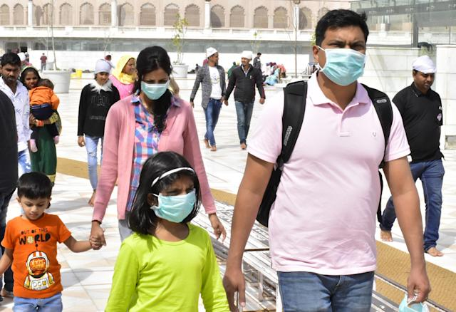 Visitors of the Golden Temple in Amritsar, India, are pictured wearing masks on 13 March. (Getty Images)