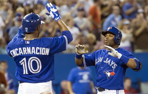 Toronto Blue Jays' Rajai Davis, right, celebrates with teammate Edwin Encarnacion (10) after hitting a three-run home run off Minnesota Twins pitcher Scott Diamond during fifth-inning AL baseball game action in Toronto, Sunday, July 7, 2013. (AP Photo/The Canadian Press, Chris Young)