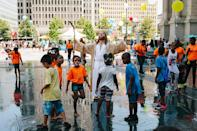 A Jesus impersonator listens to his iPhone while children play in a park in downtown Philadelphia.