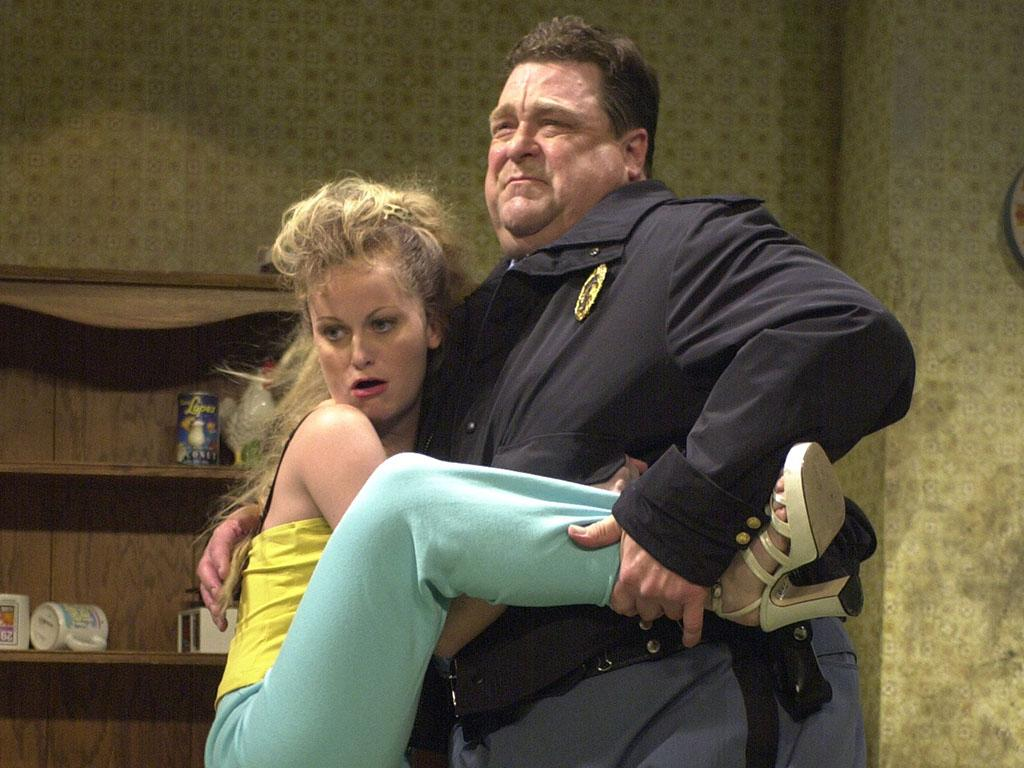 """SATURDAY NIGHT LIVE -- Episode 4 -- Air Date 11/03/2001 -- Pictured: (l-r) Amy Poehler as Gator's wife, John Goodman as police officer during the """"America Undercover"""" skit on November 3, 2001  (Photo by Mary Ellen Matthews/NBC/NBCU Photo Bank via Getty Images)"""