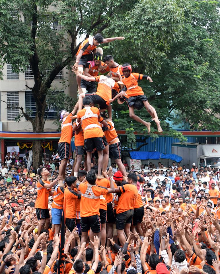 <p>Youth tumble in an attempt to form a human pyramid to break the 'Dahi Handi,' an earthen pot filled with curd hanging above, an integral part of celebrations to mark Janmashtami festival. </p>