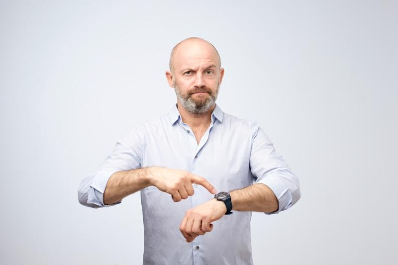 A man with a perturbed expression points to the watch on his wrist.