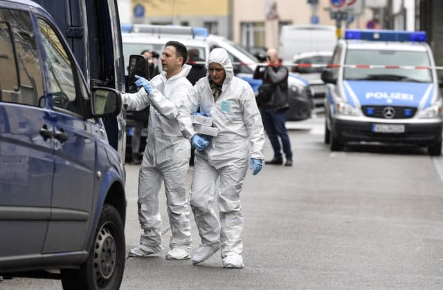 Forensic officers carry baskets from the hookah bar where several people were killed in Hanau, Germany