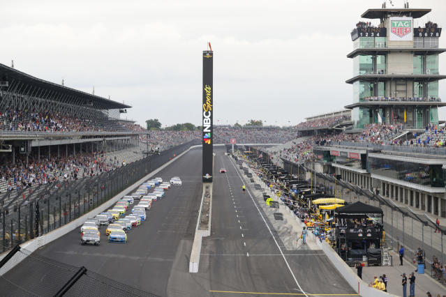 FILE - In this Sept. 8, 2019, file photo, Kevin Harvick, left, and Paul Menard lead the field into the first turn on the start of the NASCAR Brickyard 400 auto race at Indianapolis Motor Speedway, in Indianapolis. Indianapolis Motor Speedway and the IndyCar Series have been sold to Penske Entertainment Corp. in a stunning announcement that relinquishes control of the iconic speedway from the Hulman family after 74 years. (AP Photo/Michael Conroy, File)