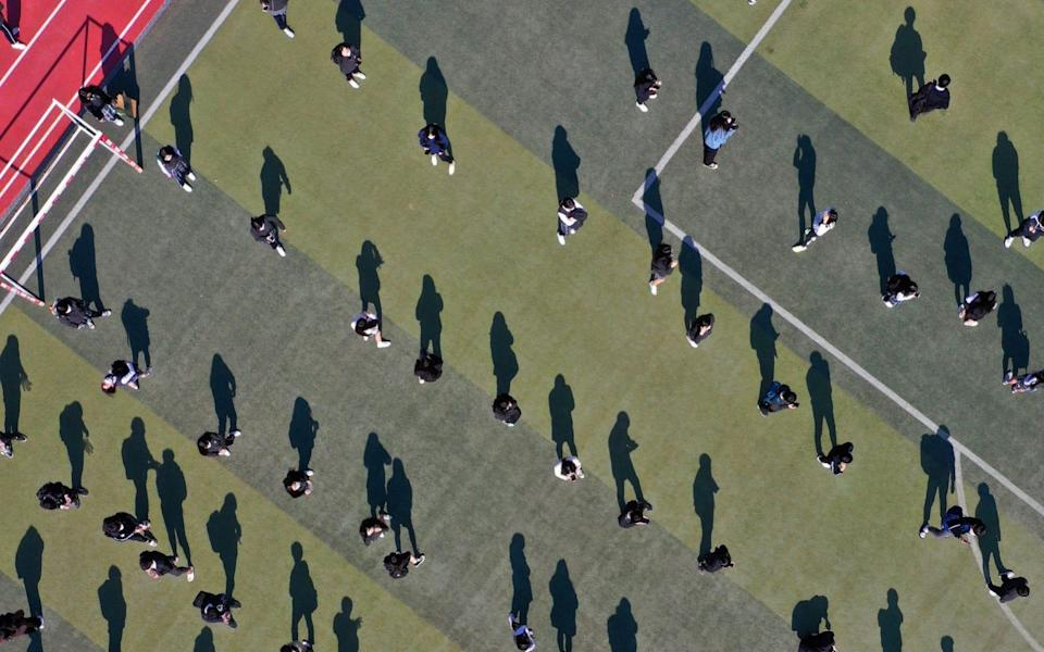 Students maintain social distance as they wait to undergo swab tests in Daegu, South Korea - YONHAP/EPA-EFE/Shutterstock