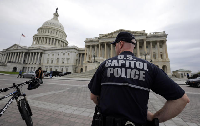 A law enforcement officer stands post at the U.S. Capitol, Monday, April 15, 2013 in Washington. Authorities say the blasts during the Boston Marathon killed two people and injured at least 73,(AP Photo/Alex Brandon)