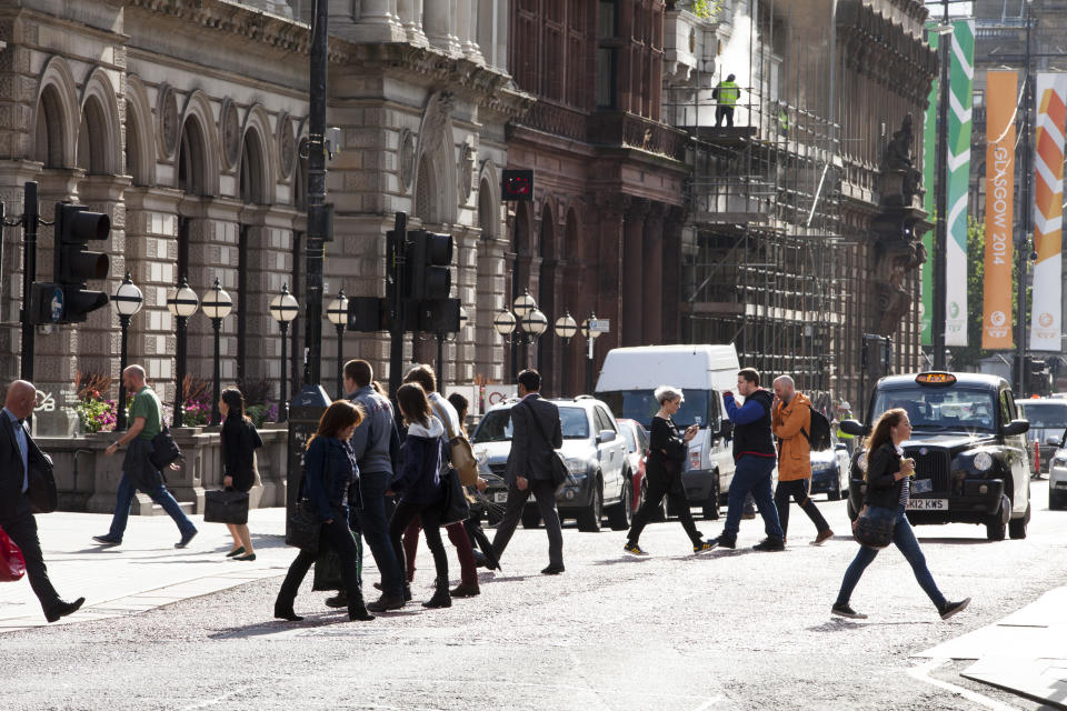 Commuters cross a downtown street during rush hour in Glasgow, Scotland
