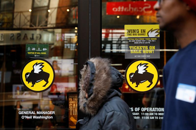 A pedestrian walks past a Buffalo Wild Wings restaurant in New York, U.S., February 6, 2017. REUTERS/Lucas Jackson