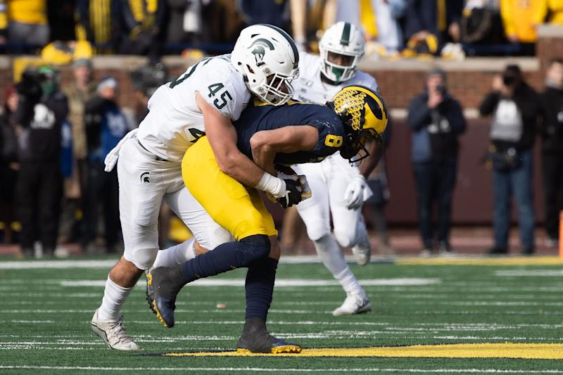 Michigan State linebacker Noah Harvey tackles Michigan wide receiver Ronnie Bell after he completed a pass during the game at Michigan Stadium on Saturday, Nov. 16, 2019.
