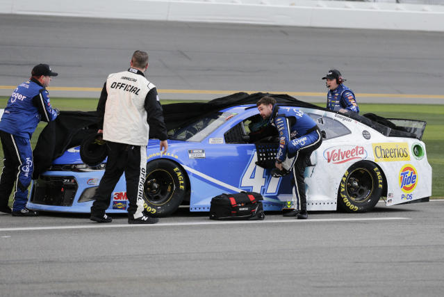 Ricky Stenhouse Jr., center, climbs out of his car as his crew covers it after rain stopped the NASCAR Daytona 500 auto race at Daytona International Speedway, Sunday, Feb. 16, 2020, in Daytona Beach, Fla. (AP Photo/Terry Renna)