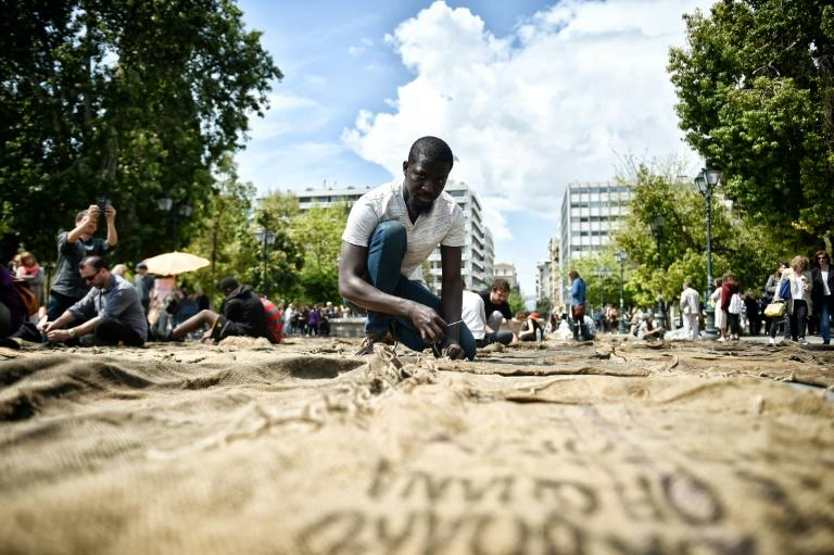 "Ghanian artist Ibrahim Mahama performs ""Check Point - Prosfygika"" on the main Syntagma square in Athens on April 7, 2017 on the eve of the opening of the 14th edition of the Documenta 14 art exhibition"