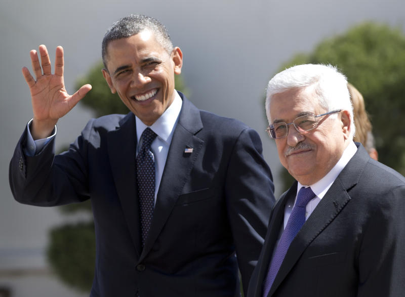 President Barack Obama waves to media as he walks with Palestinian President Mahmoud Abbas, right, as he arrives at the Muqata Presidential Compound Thursday, March 21, 2013, in the West Bank town of Ramallah. (AP Photo/Carolyn Kaster)