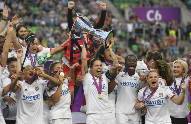 Olympique Lyon players celebrate with the trophy after they defeated FC Barcelona 4-1 in the women's soccer Champions League final match at the Groupama Arena in Budapest, Hungary, Saturday, May 18, 2019. (Tibor Illyes/MTI via AP)