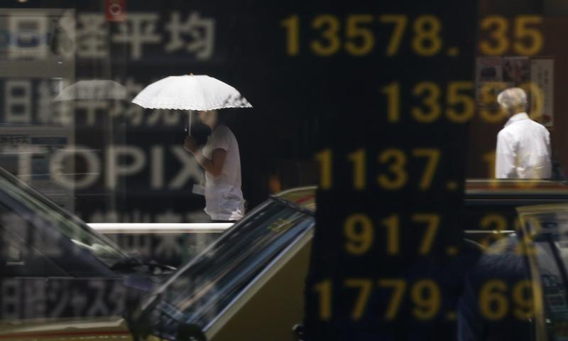 People are reflected on a stock quotation board displaying Japan's Nikkei average and other markets' indices outside a brokerage in Tokyo