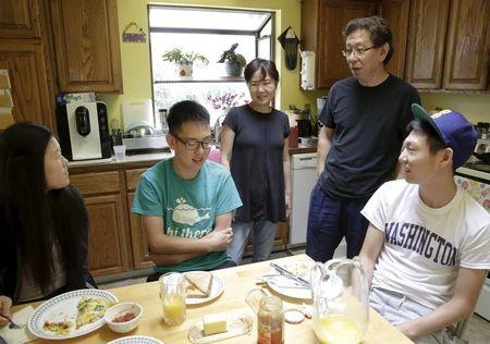 Un Bang (C) and Sung Bang (2nd R) spend time with their sons Shane (2nd L), 21, and Simon (R), 18, and Shane's girlfriend Sarah Park (L), 20, at their home in Federal Way, Washington August 8, 2015. REUTERS/Jason Redmond