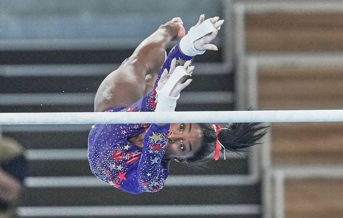 Simone Biles reaching for the uneven bars