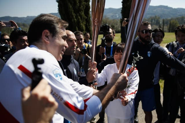 The torch of the Tokyo Olympics is passed along (Thanassis Stavrakis/AP)