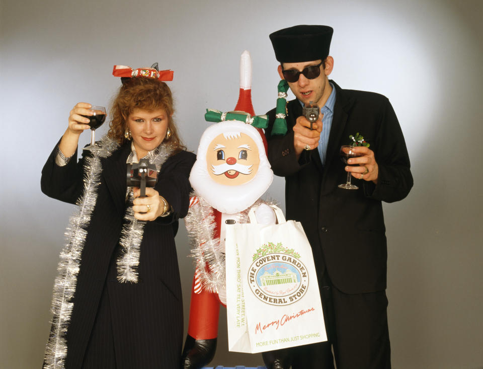 Singers Kirsty MacColl (1959 - 2000) and Shane MacGowan with with toy guns and an inflatable Santa in a festive scenario, circa 1987. In 1987, the pair collaborated on the Pogues' Christmas song 'Fairytale of New York'. (Photo by Tim Roney/Getty Images)
