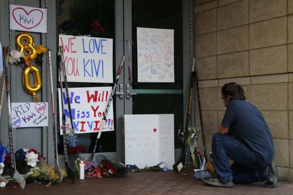 Kole Northup visits a makeshift memorial in front of Nationwide Arena Monday, July 5, 2021, in Columbus, Ohio, to remember Columbus Blue Jackets goaltender Matiss Kivlenieks who died of chest trauma from an errant fireworks mortar blast in what authorities described Monday as a tragic accident on the Fourth of July. (AP Photo/Jay LaPrete)