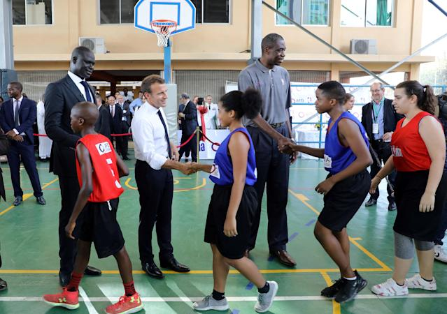 French President Emmanuel Macron and managing director of NBA Africa Amadou Gallo Fall (L) greet young basketball players during a meeting with former pro NBA Africa basketball players at the French Louis Pasteur high school in Lagos, Nigeria, July 4, 2018. Ludovic Marin/Pool via Reuters