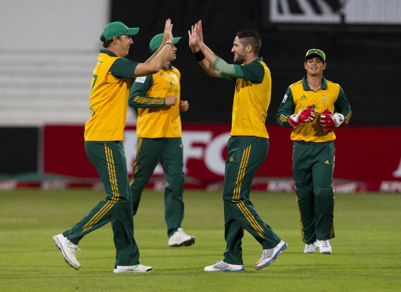 South Africa's Kyle Abbott (L) and Wayne Parnell celebrate taking the wicket of Australia's Shane Watson as Quinton de Kock (R) looks on during the cricket T20 International cricket match in Durban, March 12, 2014. REUTERS/Rogan Ward (SOUTH AFRICA - Tags: SPORT CRICKET)
